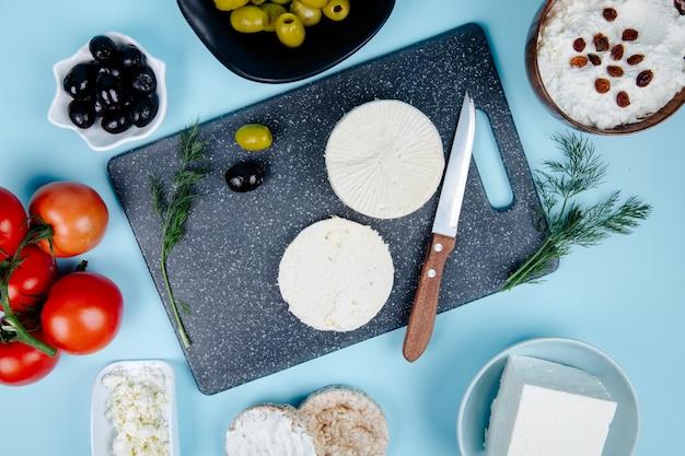 Draufsicht des ziegenkäses auf einer tafel mit einem küchenmesser und eingelegten oliven der frischen tomaten und hüttenkäse in einer schüssel auf blau