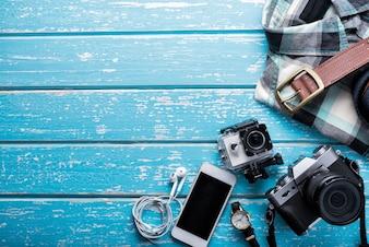 Draufsicht des Zubehörs des Reisenden, flache Laienphotographie des Reisekonzeptes auf blauem Hintergrund