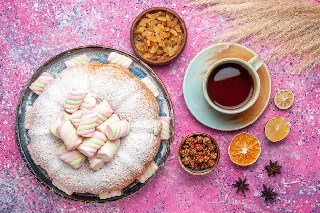 Draufsicht des zuckerpulverkuchens mit süßen marshmallows und einer tasse tee auf rosa oberfläche