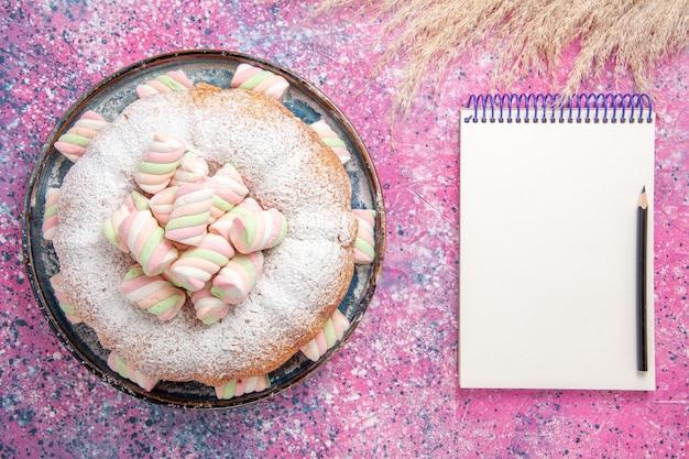 Draufsicht des zuckerpulverkuchens mit süßen marshmallows und notizblock auf rosa oberfläche