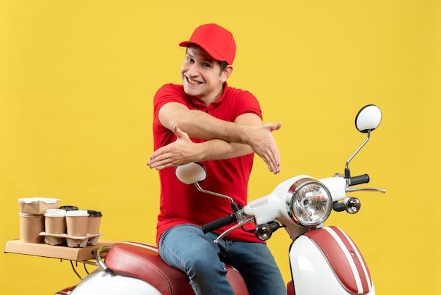 Draufsicht des zufriedenen jungen kerls, der rote bluse und hut trägt, die aufträge liefern, die jemanden auf gelbem hintergrund begrüßen