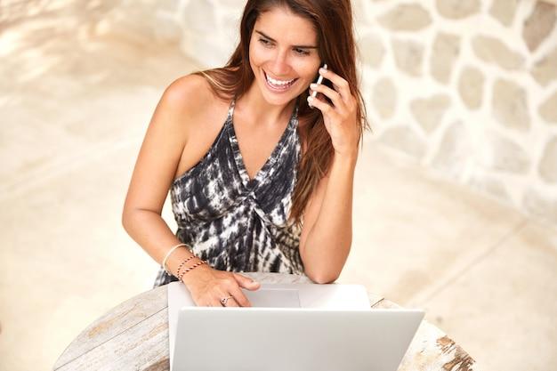 Draufsicht des zufriedenen weiblichen modells, das in der cafeteria neu erstellt wird, hat gespräch mit bester freundin auf smartphone, arbeitet ferngesteuert auf laptop, verbunden mit drahtlosem hochgeschwindigkeitsinternet. freiberuflerin