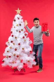 Draufsicht des zuversichtlichen jungen mannes, der nahe dem geschmückten weißen weihnachtsbaum steht und seine geschenke hält und fünf auf rot zeigt