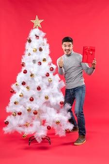 Draufsicht des zuversichtlichen jungen mannes, der nahe dem verzierten weißen neujahrsbaum steht