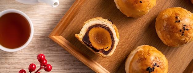 Draufsicht-designkonzept von mondkuchen-eigelb-gebäck, mondkuchen für mid-autumn-festival-urlaub auf holztischhintergrund