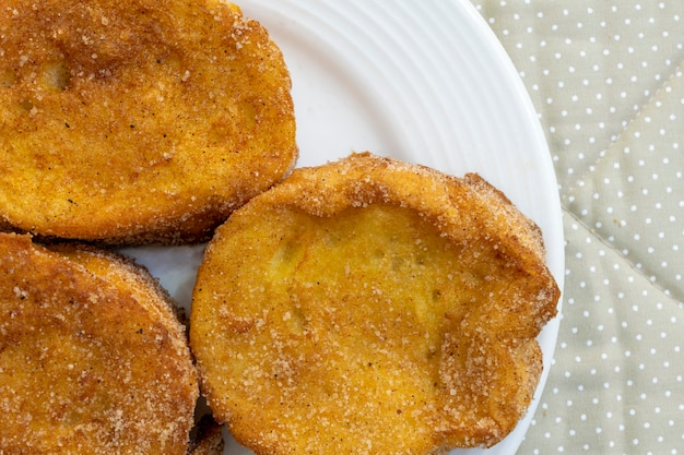 Draufsicht detail des gebackenen oder gebratenen brotes mit zucker und zimt. dessert namens rabanada, torrija oder goldenes brot.