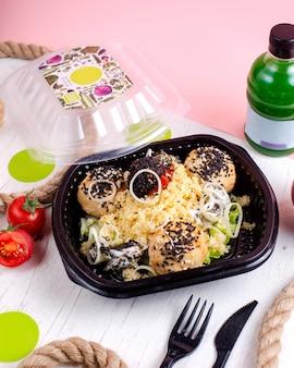 Draufsicht diätkost gekochte hühnerfleischbällchen mit zwiebel und tomate mit hirse und entgiftungsflasche