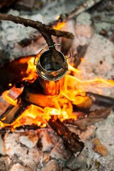 Draufsicht, die das wasser über einem lagerfeuer erhitzt