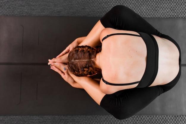 Draufsicht, die yoga zu hause konzept praktiziert