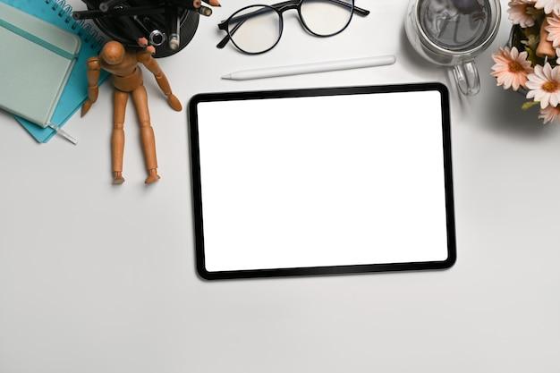 Draufsicht, digitale tablette mit leerem bildschirm auf weißem schreibtisch.