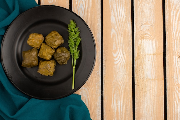 Draufsicht dolma grüner dolma mit hackfleisch in schwarzer platte auf dem braunen holzschreibtisch