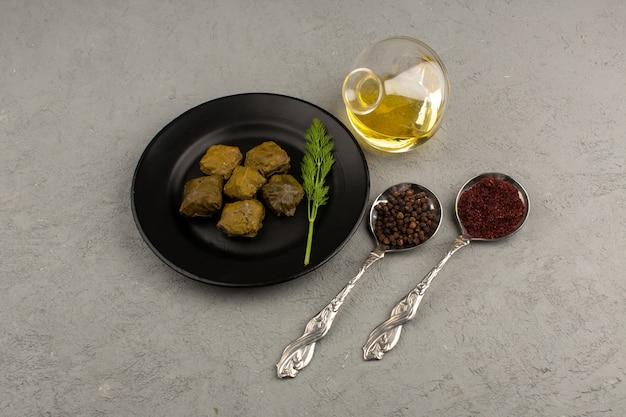 Draufsicht dolma in schwarzer platte zusammen mit olivenöl auf dem grauen schreibtisch