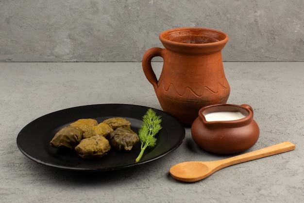 Draufsicht dolma lecker mit hackfleisch in schwarzer platte zusammen mit joghurt auf dem grauen