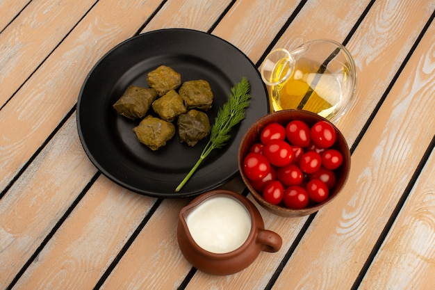 Draufsicht dolma mit hackfleisch in schwarzer platte zusammen mit joghurt und olivenöl auf dem holzboden