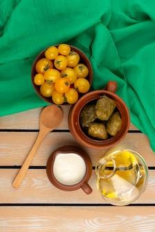 Draufsicht dolma mit joghurt zusammen mit gelben tomaten und olivenöl auf dem grünen taschentuch und dem rustikalen holzboden