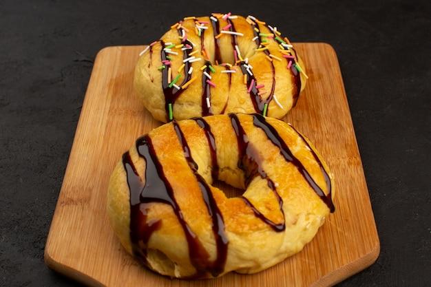 Draufsicht donuts lecker lecker süß mit schokolade auf dem braunen schreibtisch und dunkel