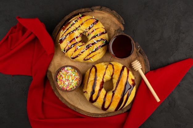 Draufsicht donuts süß lecker lecker auf dem braunen schreibtisch und dunklem hintergrund