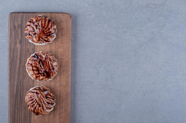 Draufsicht. drei frische kekse auf holzbrett