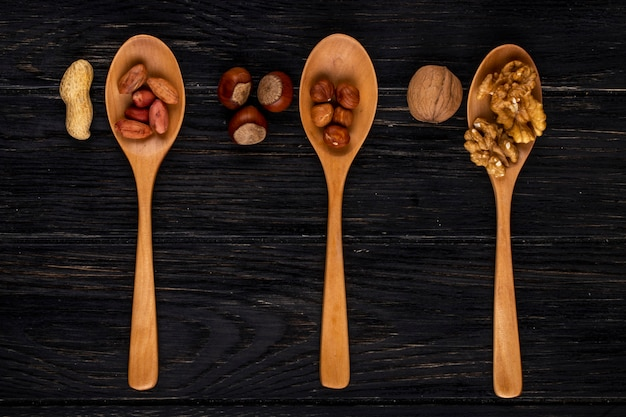 Draufsicht drei holzlöffel mit haselnüssen erdnüssen und walnüssen geschält und in der schale