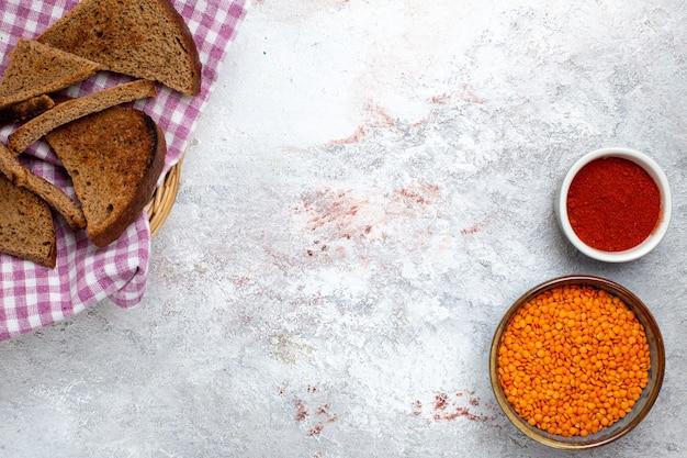 Draufsicht dunkle brotlaibe mit orange rohen bohnen auf weißem backgrond-brötchen-copybook-essen