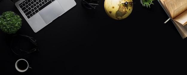 Draufsicht dunkler und schwarzer hintergrund mit laptop und buch und lernen von geographie und geschichte mit globalem erdkartenball, bildungskonzept