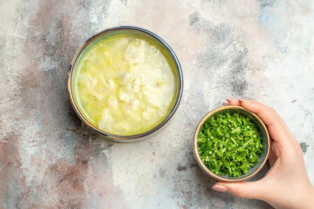 Draufsicht dushbara knödel suppengrün in schüssel in weiblicher hand auf nackter oberfläche mit kopierraum