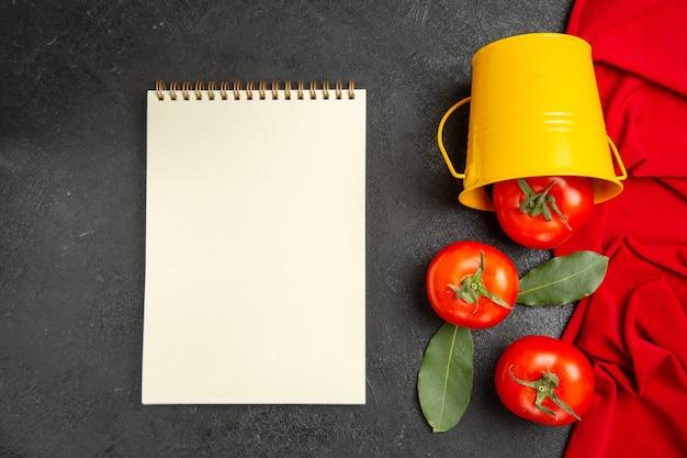 Draufsicht eimer mit roten tomaten rotes handtuch und ein notizbuch auf dunklem hintergrund