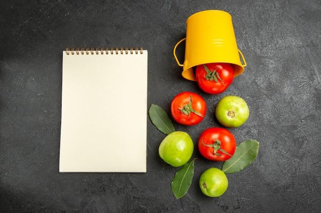 Draufsicht eimer mit roten und grünen tomaten lorbeerblättern und einem notizbuch auf dunklem hintergrund