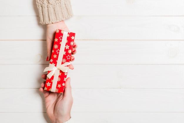 Draufsicht ein mann und eine frau, die ein geschenk auf hölzernem halten. geben und empfangen eines vorhandenen exemplars