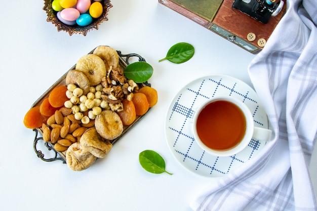 Draufsicht eine art nüsse mit getrockneten aprikosen und getrockneten feigen auf einem tablett mit einer tasse tee