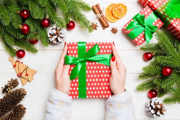 Draufsicht eine frau, die eine geschenkbox in ihren händen auf festlichem hölzernem hält. tanne und weihnachtsschmuck. zeit