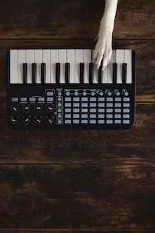 Draufsicht eine hundepfote auf midi-klavier kompakter kabelloser tastaturmischer spielt melodie.