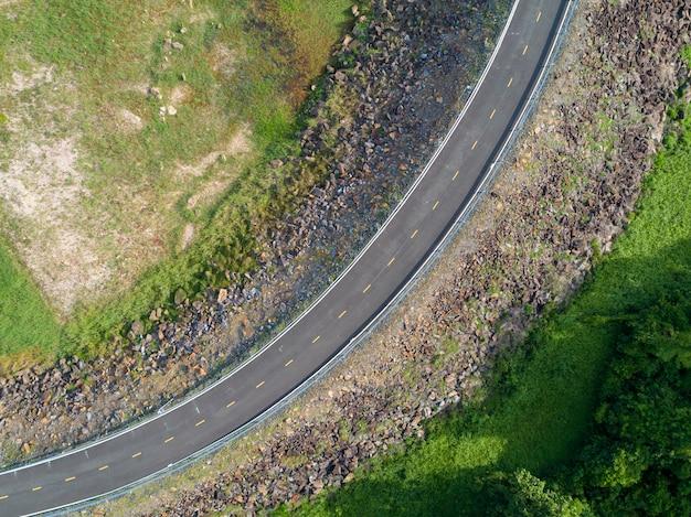 Draufsicht eine leere kurvenreiche asphaltstraße mit grünen bäumen und straßenrand des grases om von der brummenvogelperspektive von oben.