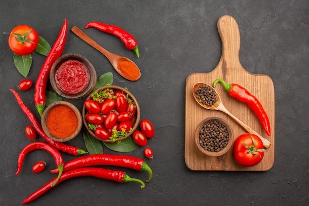 Draufsicht eine schüssel kirschtomaten heiße rote paprika lorbeerblätter und eine schüssel schwarzer pfeffer ein löffel eine tomate ein roter pfeffer auf dem schneidebrett auf schwarzem grund