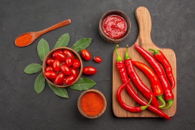 Draufsicht eine schüssel kirschtomaten lorbeerblätter scharfe rote paprikaschoten auf dem schneidebrett ein holzlöffel und schalen mit ketchup und paprikapulver auf dem schwarzen tisch