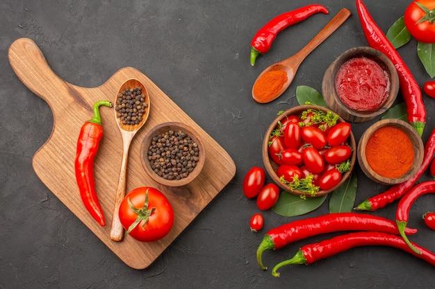 Draufsicht eine schüssel kirschtomaten rote paprika lorbeerblätter und eine schüssel schwarzer pfeffer ein löffel eine tomate ein roter pfeffer auf dem schneidebrett auf schwarzem grund