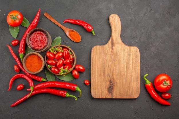 Draufsicht eine schüssel kirschtomaten scharfe rote paprikaschoten ein holzlöffel lorbeerblätter schalen mit ketchup und paprikapulver ein schneidebrett und tomate auf schwarzem grund