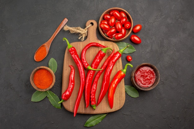 Draufsicht eine schüssel kirschtomaten scharfe rote paprikaschoten ein schneidebrett ein holzlöffel lorbeerblätter und schalen mit ketchup und paprikapulver auf dem schwarzen tisch