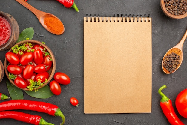 Draufsicht eine schüssel kirschtomaten scharfe rote paprikaschoten schwarzer pfeffer in einem holzlöffel schalen mit ketchup und schwarzem pfeffer und ein notizbuch auf schwarzem grund