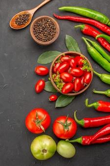 Draufsicht eine schüssel kirschtomaten scharfe rote und grüne paprikaschoten und tomaten schwarzer pfeffer in einem holzlöffel eine schüssel schwarzen pfeffers auf schwarzem hintergrund