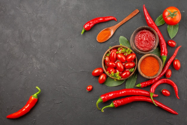Draufsicht eine schüssel mit kirschtomaten scharfen roten paprikaschoten ein holzlöffel lorbeerblätter schalen mit ketchup und paprikapulver und tomaten auf schwarzem grund