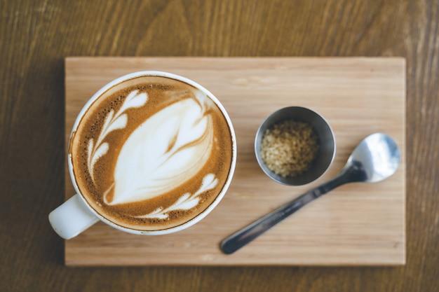 Draufsicht eine tasse kaffee lattekunst im kaffeestube-café auf hölzernem brett