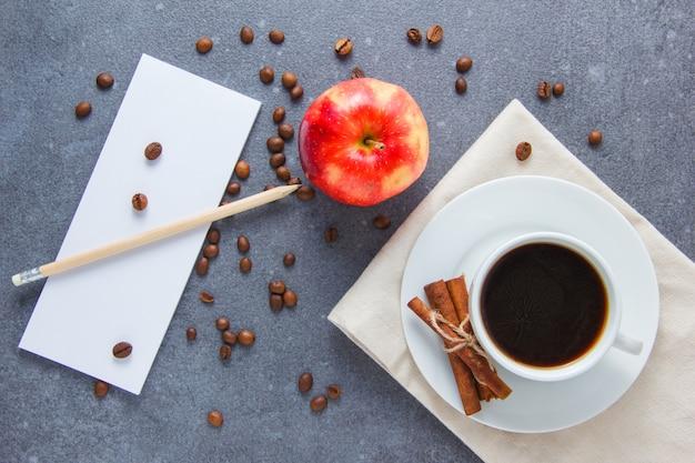 Draufsicht eine tasse kaffee mit apfel, trockenem zimt, bleistift und notizbuch auf grauer oberfläche. horizontal