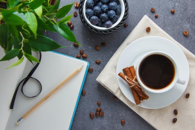 Draufsicht eine tasse kaffee mit blaubeeren, trockenem zimt, pflanze, bleistift und notizbuch auf grauer oberfläche. horizontal