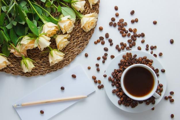 Draufsicht eine tasse kaffee mit blumen auf einem untersetzer, kaffeebohnen, bleistift und papier auf weißer oberfläche. horizontal