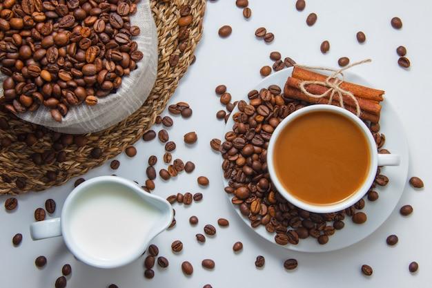 Draufsicht eine tasse kaffee mit kaffeebohnen, milch, trockenem zimt auf untersetzer und weißer oberfläche. horizontal