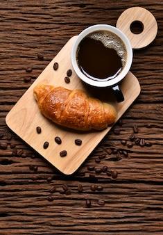 Draufsicht eine tasse kaffee mit kaffeebohnen und croissant auf holztisch