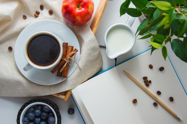 Draufsicht eine tasse kaffee mit milch, apfel, trockenem zimt, blaubeeren, pflanze, bleistift und notizbuch auf weißer oberfläche. horizontal