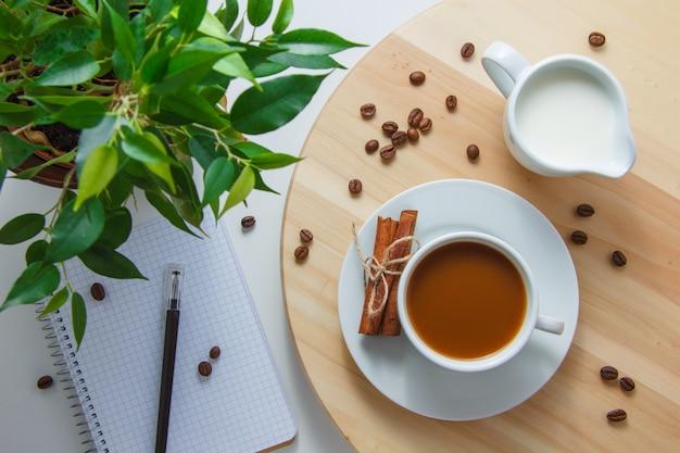 Draufsicht eine tasse kaffee mit pflanze, kaffeebohnen, milch, trockenem zimt, notizbuch und stift auf plattform und weißer oberfläche. horizontal