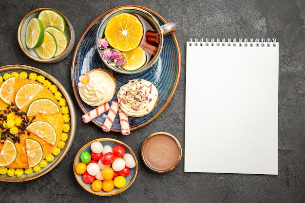 Draufsicht eine tasse kräutertee blauer teller mit cupcakes mit sahne eine tasse kräutertee und süßigkeiten neben dem weißen notizbuch und den schalen mit zitrusfrüchten schokoladencreme und bonbons auf dem tisch